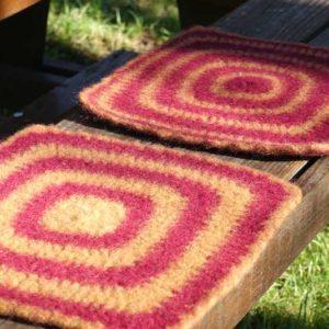 Gehäkelte Sitzkissen aus Filzwolle auf einer Gartenbank